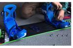 スノーボードの板にビンディングを取り付けている図